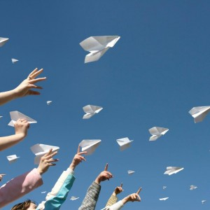 hands sending paper airplanes square